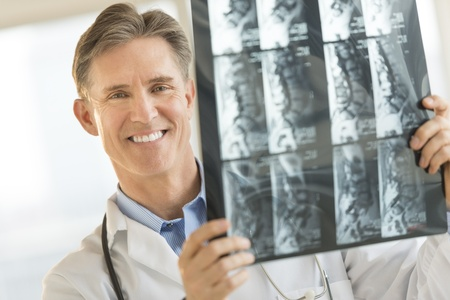 Portrait of confident male doctor with X-ray image smiling while standing in clinic Banco de Imagens