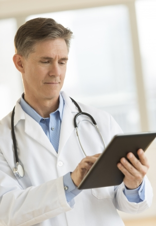 Mature male doctor using digital tablet while standing in clinic Standard-Bild