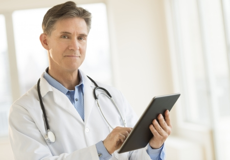 Portrait of confident mature male doctor holding digital tablet while standing in clinic Standard-Bild