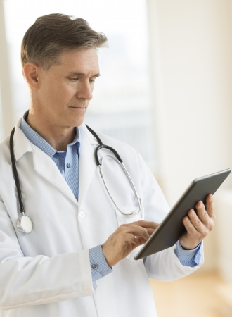 Mature male doctor touching digital tablet while standing in clinic Standard-Bild