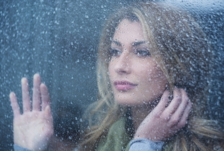 Thoughtful young woman looking through glass window with raindrops