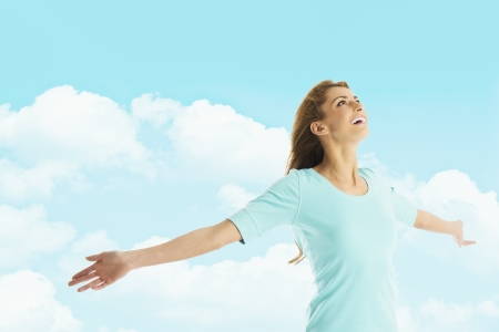 Happy young woman with arms outstretched looking up while standing against cloudy sky