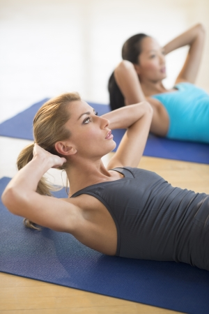 Beautiful young woman exercising with female friend at gym