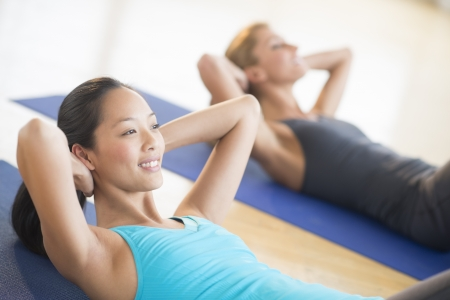 back exercise: Mid adult woman smiling while doing sit-ups at gym with female friend in background Stock Photo