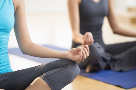 Cropped image of women practicing yoga while sitting on exercise mat at gym