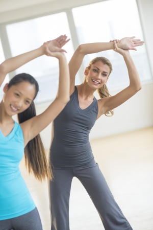 three people only: Front view of happy female friends doing stretching exercise at gym