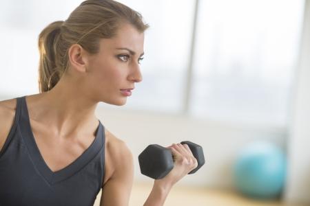 Dedicated young woman lifting weights at health club