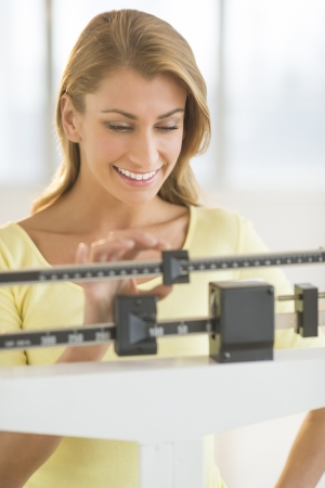 Happy young Caucasian woman weighing herself on balance scale at health club Standard-Bild