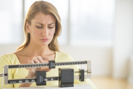 weight scale: Young Caucasian woman using balance weight scale at gym Stock Photo