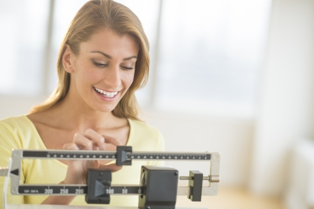 health club: Happy young woman weighing herself on balance scale at health club Stock Photo