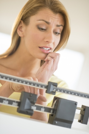 Worried young Caucasian woman using balance weight scale at health club photo