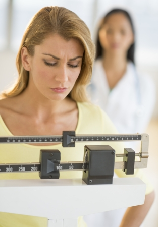 Beautiful young woman weighing herself on balance weight scale with doctor standing in background at clinic Stock Photo