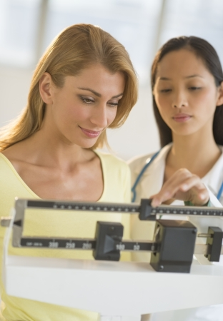 mid adult female: Mid adult female doctor weighing woman on balance weight scale in clinic Stock Photo