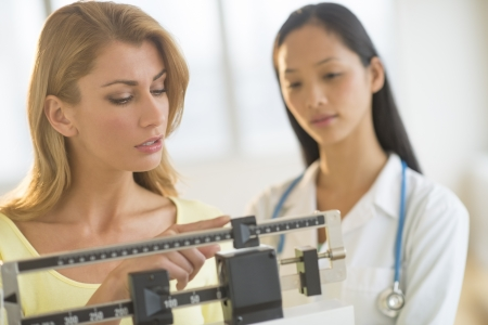 Young woman adjusting balance weight scale while standing by female doctor in clinic Standard-Bild