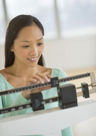 gewicht skala: Mid erwachsenen asiatischen Frau l�chelnd, w�hrend mit Balance Waage im Fitness-Studio
