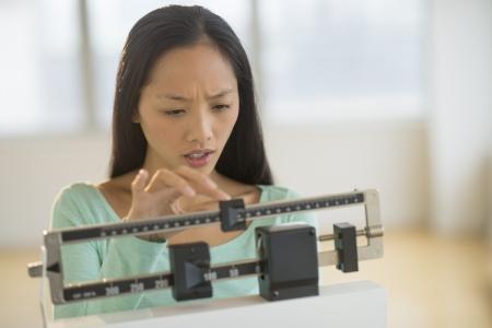 gewicht skala: Schockiert Mitte erwachsenen Frau Anpassung Balance Waage im Fitnessstudio Lizenzfreie Bilder