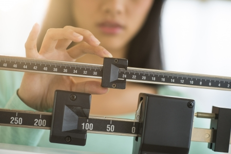 Midsection of mid adult Asian woman adjusting balance weight scale photo
