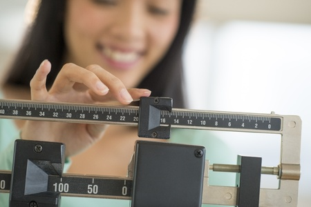 weight control: Midsection of mid adult Asian woman smiling while adjusting balance weight scale Stock Photo