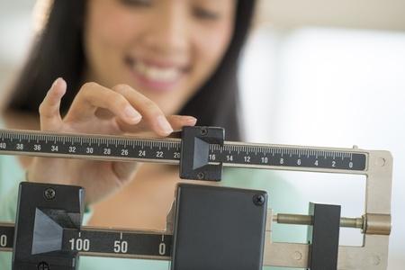 gewicht skala: Mittlerer Teil von Mitte erwachsenen asiatischen Frau l�chelt, w�hrend die Anpassung Balance Waage