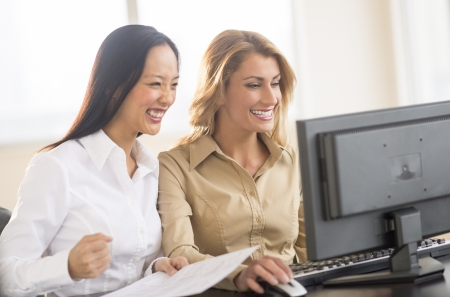 using computer: Successful multi-ethnic businesswomen using computer at desk in office