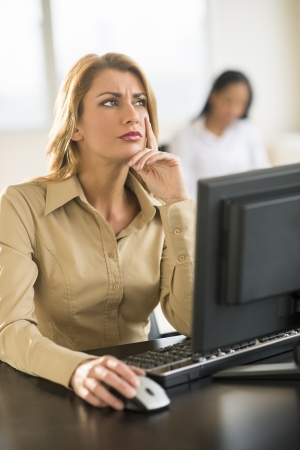 two persons only: Thoughtful young businesswoman using computer at desk in office with female colleague sitting in background