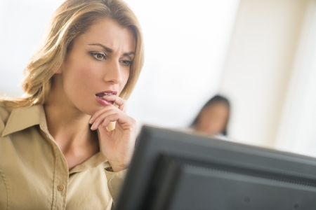 two persons only: Close-up of nervous young businesswoman looking at computer with colleague in background Stock Photo