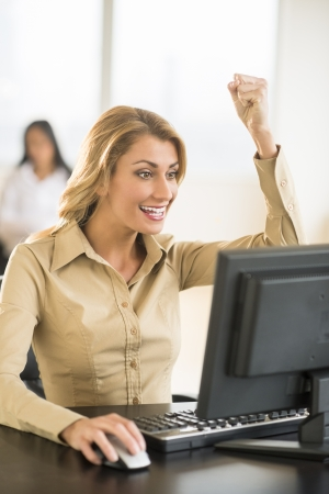 good news: Successful young businesswoman using computer at desk with female colleague sitting in background Stock Photo