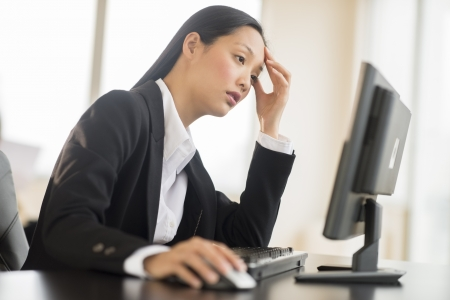 one mid adult woman only: Overworked mid adult businesswoman working on computer at desk in office Stock Photo