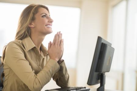 mujer rezando: Empresaria joven feliz con las manos juntas orando mientras estaba sentado en el escritorio en la oficina