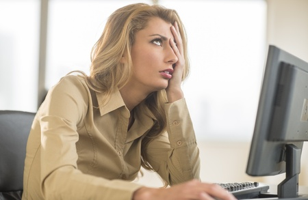 Frustrated young businesswoman looking up while sitting at computer desk