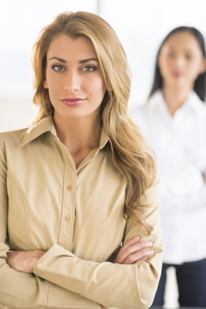 Portrait of confident businesswoman standing arms crossed at office with female colleague in background photo