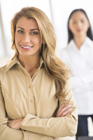 Portrait of beautiful businesswoman standing arms crossed at office with female colleague in background