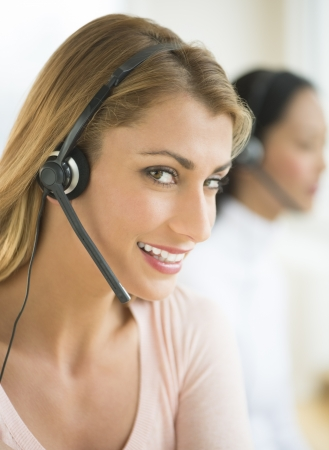 Close-up of portrait of happy female customer service representative wearing headset with colleague in background photo