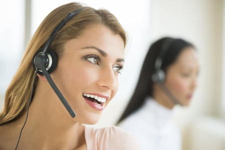 telephonist: Close-up of happy female customer service representative looking away with colleague in background
