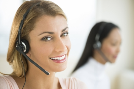 telephonist: Close-up portrait of happy female customer service representative with colleague in background