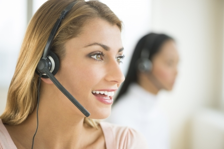 telephonist: Happy female customer service representative looking away with colleague in background Stock Photo