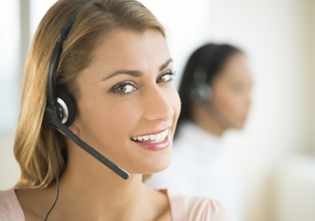 telephonist: Close-up portrait of female customer service representative smiling with colleague in background Stock Photo