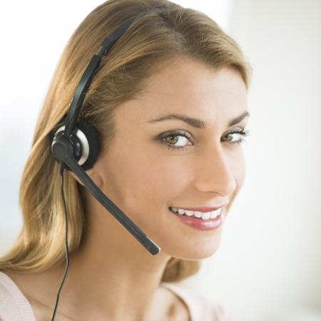 telephonist: Close-up portrait of happy female customer service representative wearing headset