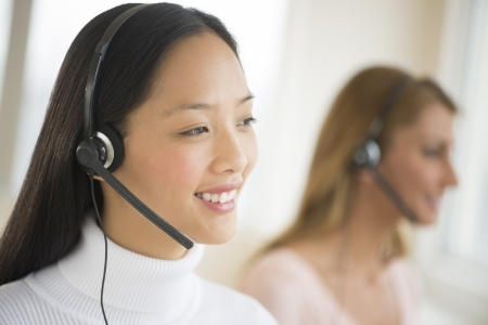 customer service representative: Happy female customer service representative wearing headset looking away with colleague in background Stock Photo