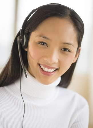 service: Portrait of happy Asian female customer service representative wearing headset Stock Photo
