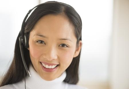 Portrait of happy mid adult female customer service representative wearing headset