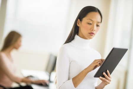 Mid adult businesswoman using digital tablet in office with female colleague sitting in background photo