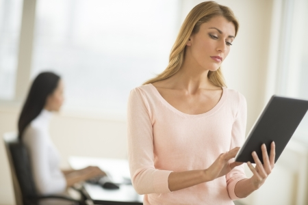 Young Caucasian businesswoman using digital tablet at office with female colleague in background photo