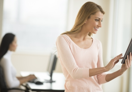 Happy young businesswoman using digital tablet in office with female colleague working in background