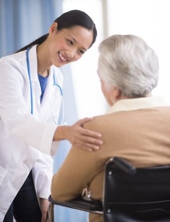 wheelchairs: Happy mid adult Asian female doctor consoling senior woman sitting in wheelchair Stock Photo
