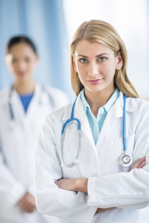 Portrait of confident female doctor standing arms crossed with colleague in background at clinic