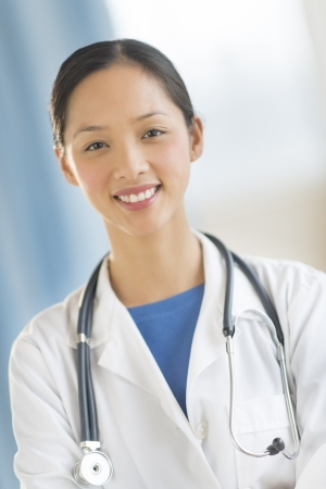 mid adult female: Front view portrait of happy mid adult female doctor smiling while standing in clinic Stock Photo