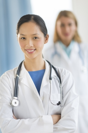 Portrait of confident Asian female doctor standing arms crossed with colleague in background at clinic Stock Photo - 22143633