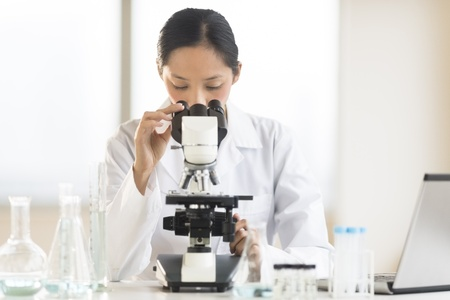 Mid adult Asian female doctor using microscope at desk in laboratory