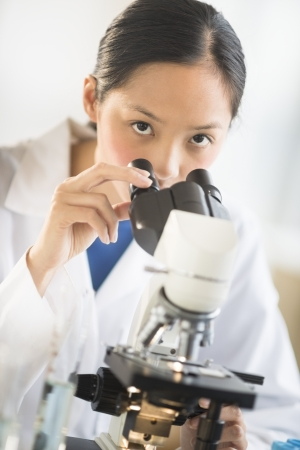 mid adult female: Portrait of Asian mid adult female scientist using microscope in laboratory